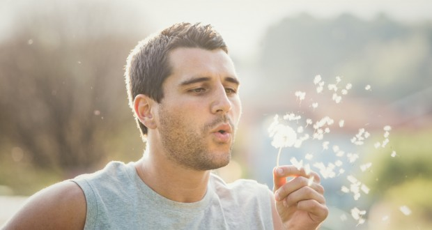 Young man playing with dandelion